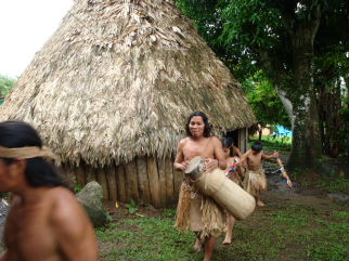Maleku Indians in bark cloth dress leaving traditional grass hut in the village of Tonjibe, Costa Rica